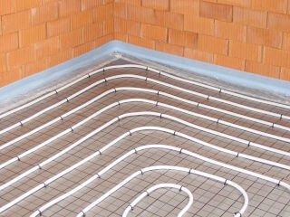 Fußbodenheizung im Tackersystem - Eckansicht mit verlegter Rasterfolie und Rohr befestigt mit Tackernadeln